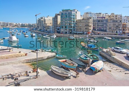 ST JULIANS, MALTA - SEPTEMBER 13, 2015: Small boats moored in St Julians and Spinola bay on a sunny summer day on September 13, 2015 in St Julians, Malta.