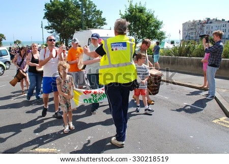 ST.LEONARDS-ON-SEA, ENGLAND - JULY 11, 2015: A marshal guides people taking part in the parade at the annual St.Leonards Festival in Warrior Square.The free entertainment event was first held in 2006. - stock photo