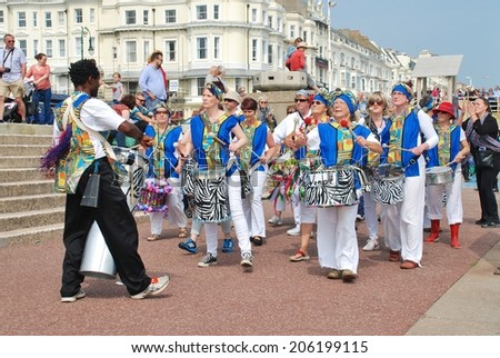 ST.LEONARDS-ON-SEA, ENGLAND - JULY 12, 2014: Dende Nation, Samba drum troupe, perform during a parade on the seafront at the annual St.Leonards Festival. The community event was first held in 2006. - stock photo