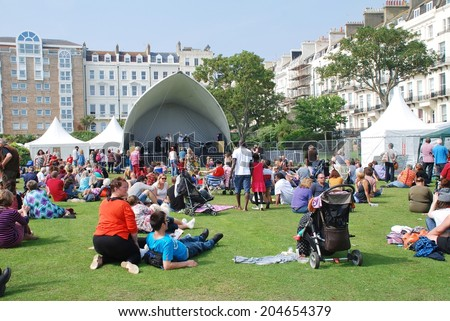 ST.LEONARDS-ON-SEA, ENGLAND - JULY 12, 2014: The audience sit on the grass at the annual St.Leonards Festival. The free music and entertainment community event was first held in 2006. - stock photo