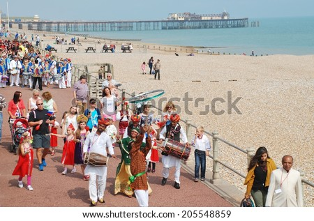 ST.LEONARDS-ON-SEA, ENGLAND - JULY 12, 2014: The Musifar Gypsies of Rajasthan, Indian music group, lead the parade on the seafront at the annual St.Leonards Festival. The event was first held in 2006. - stock photo