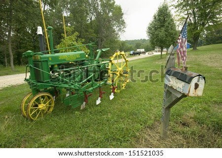 ST. LOUIS COUNTY, MISSOURI - CIRCA 2006: Antique John Deere tractor in front of yard along Manchester Road, Missouri - stock photo
