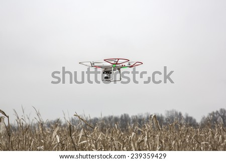 St.Louis Missouri. - DECEMBER19: Editorial photo of a DJI Phantom drone in flight with a mounted GoPro Hero3 Black Edition digital camera on December 19, 2014 in St.Louis Missouri over corn field - stock photo