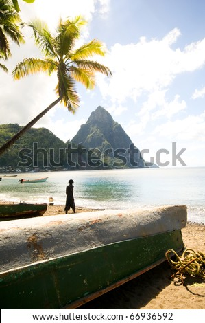 St. Lucia island view of famous twin piton mountain peaks from Soufriere beach native fishing boats Rasta man fisherman silhouette  in Caribbean Sea - stock photo
