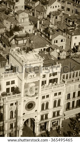 St Mark's Clocktower with Zodiac clock and Winged Lion. A view from the Campanile tower at Piazza San Marco in Venice (Italy). Aged photo. Sepia. - stock photo