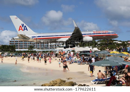 ST. MARTIN - FEBRUARY 8: An American Airlines Boeing 757 approaching on February 8, 2014 in St. Martin. St. Martin is rated one of the most dangerous airports in the world. - stock photo