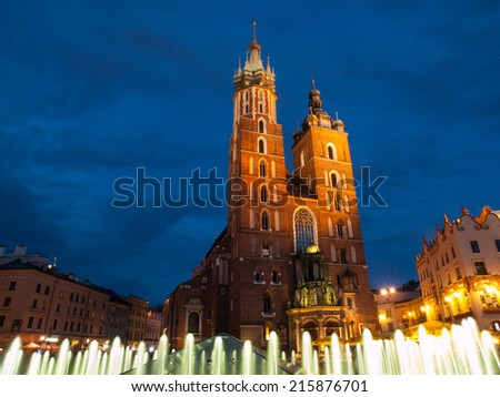 St. Mary's Church with two different towers by night (Krakow, Poland). Viewed from fountain. - stock photo