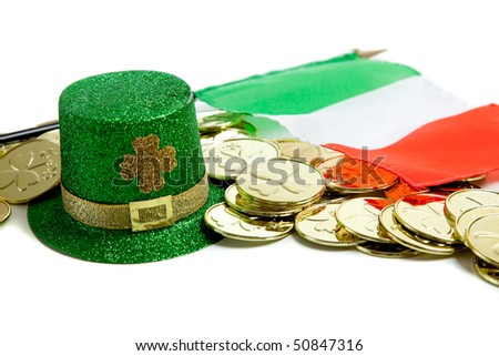 St. Patrick's day decorations including gold coins, green glittery leprecaun hat and irish flag on a white background - stock photo