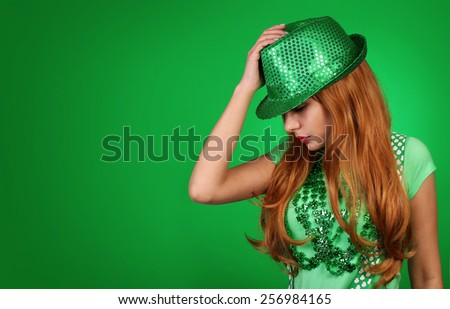 St. Patrick's day Girl. Young woman wearing hat over green background - stock photo