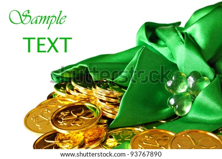 St. Patrick's day image of shiny gold shamrock coins spilling from a green satin bag with glass shamrock charm.  Macro on white background with copy space.