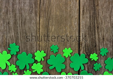 St Patricks Day bottom border of shamrocks over a rustic wooden background - stock photo
