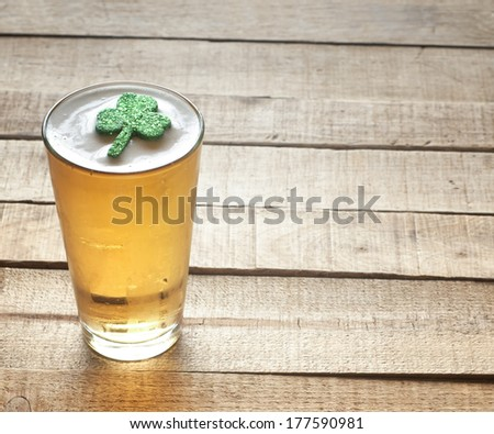 St. Patricks Day green shamrock floating in a cold, frosty glass of beer on a rustic wood background with room or space for copy, text, words. - stock photo