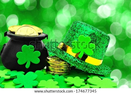 St Patricks Day Pot of Gold, hat and shamrocks over a green background - stock photo