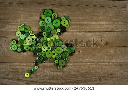 St Patricks Day shamrock made of buttons against an old wood background - stock photo