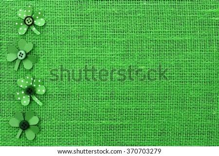 St Patricks Day side border of handmade paper shamrocks over a green burlap background - stock photo