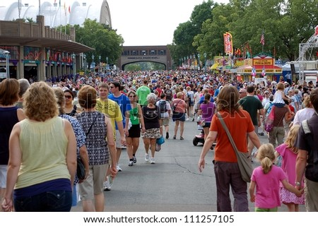 ST. PAUL - AUGUST 26:  Large crowds fill the street at the Minnesota State Fair on August 26, 2012, in St. Paul.  Attendance is averaging 139,000 per day in 2012. - stock photo