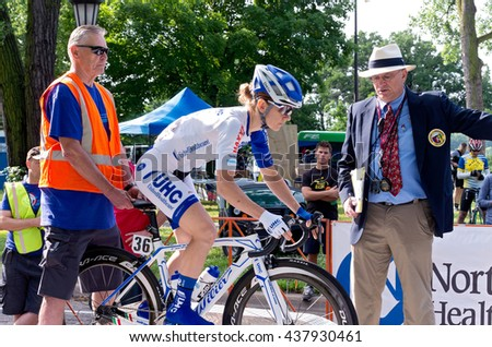 ST. PAUL, MINNESOTA - JUNE 15, 2016: The annual North Star Grand Prix pro cycling event begins with a stage one time trial in St. Paul on June 15 as officials assist a racer at the starting ramp.  - stock photo