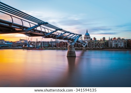 St Paul's Cathedral and the Millennium bridge at sunset in London, UK. - stock photo