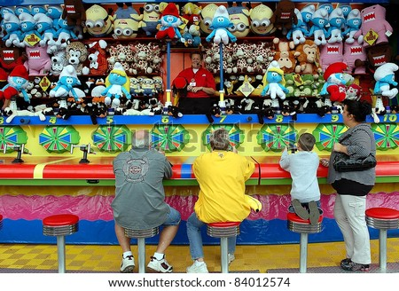 ST. PAUL - SEPTEMBER 4:  Fair goers try their luck at arcade games at the Minnesota State Fair, on Sept. 4, 2011 in St. Paul, Minnesota.  Attendance at the fair has averaged 138,000 per day. - stock photo