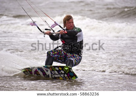 ST. PETER-ORDING, GERMANY - JULY 24: Professional kite-surfer Fabian Bertschat, Germany, demonstrating his ability on the Palmolive Kitesurf Worldcup 2010, July 24, 2010 in St. Peter-Ording, Germany