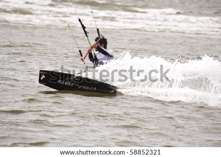 ST. PETER-ORDING, GERMANY - JULY 22: Unidentified professional  kite-surfer demonstrates his ability on the Palmolive Kitesurf Worldcup 2010 in St. Peter-Ording, July 22, 2010 in St. Peter-Ording, Germany