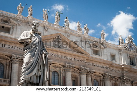 St. Peter, Vatican City. Low angle view of the statue of St. Peter in St. Peter's Square, Vatican City, with the front of the famous Basilica in the background. - stock photo