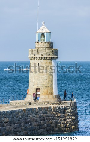 St Peters Port Lighthouse in Guernsey. Guernsey (officially the Bailiwick of Guernsey) is a British Crown dependency in English Channel off the coast of Normandy. - stock photo