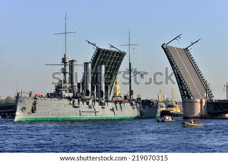 """St. Petersburg. Passage of cruiser """"Aurora"""" under """"the Palace"""" bridge. The cruiser is towed to the docks Kronstadt Naval factory - stock photo"""