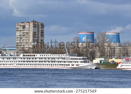 ST.PETERSBURG, RUSSIA - APRIL 26, 2015: Bank of the river Neva on the outskirts of St. Petersburg. Residential buildings and river cruise ship.
