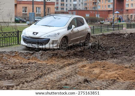 ST. PETERSBURG, RUSSIA - CIRCA APR, 2015: Car is wrong parked and left on lawn while machinery makes urban land improvement. Russia apartment courtyard with parking lot - stock photo