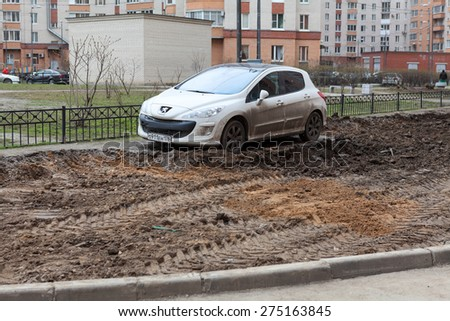 ST. PETERSBURG, RUSSIA - CIRCA APR, 2015: Vehicle is wrong parked and left on lawn while machinery makes urban land improvement. Russia apartment courtyard with parking lot - stock photo