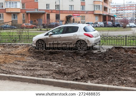 ST. PETERSBURG, RUSSIA - CIRCA APR, 2015: Wrong parking car is on middle of lawn while construction machinery works for extension of parking area of apartment building. Creation of living environment - stock photo