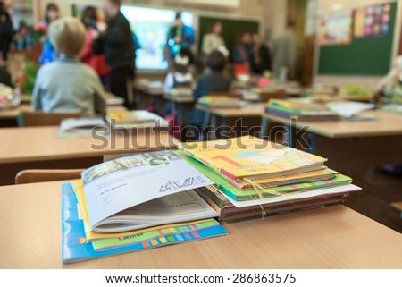 ST. PETERSBURG, RUSSIA - CIRCA SEPTEMBER, 2014: School exercise and ABC books are on the desk in classroom. Parents with kids are indoor. Children go back to school at first time in September