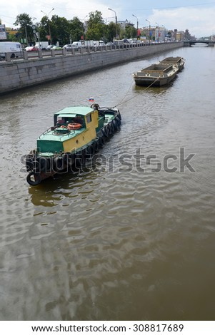 ST. PETERSBURG, RUSSIA - JULY 23, 2015: The tow pulls gruntootvozny barges on the Bypass channel