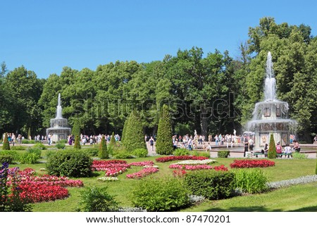 ST. PETERSBURG, RUSSIA - JULY 02:Tourists visit the sights of the lower park of Peterhof (after the solemn opening of the fountains) on July 02, 2011 in St. Petersburg, Russia. - stock photo