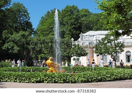 ST. PETERSBURG, RUSSIA - JULY 02:Tourists visiting the sights of the lower park of Peterhof (after the solemn opening of the fountains) on July 02, 2011 in St. Petersburg, Russia. - stock photo