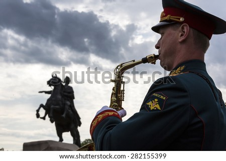 ST PETERSBURG,RUSSIA-MAY 27:A military band plays music during laying flowers at the monument of Peter the Great on the Senate Square in St. Petersburg on 27 of May 2015, Russia  - stock photo