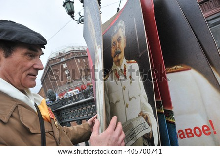 ST. PETERSBURG, RUSSIA - MAY1: Man with portrait of Soviet dictator Josef Stalin takes part in the May day demonstration in May 1, 2010