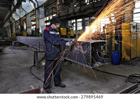 St. Petersburg, Russia - May 18, 2015: Metalworker grinds weld seam steel sections using Angle Grinding Machines, plant for the production of metal constructions.