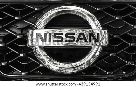 St-Petersburg, Russia - May 15, 2016: Nissan car logo on a front radiator grille of Nissan X-Trail SUV, closeup photo with selective focus - stock photo