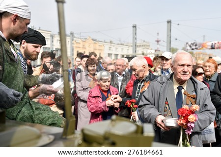 ST. PETERSBURG, RUSSIA - MAY 7, 2015: WWII veterans at the field kitchen during the parade of steam locomotives. The event dedicated to the WWII Victory Day