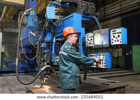 St. Petersburg, Russia - October 10, 2014: Automatic submerged arc welding, the working operator controls the welding robot, standing at the control panel. Butt welding machine for steel sheets.  - stock photo