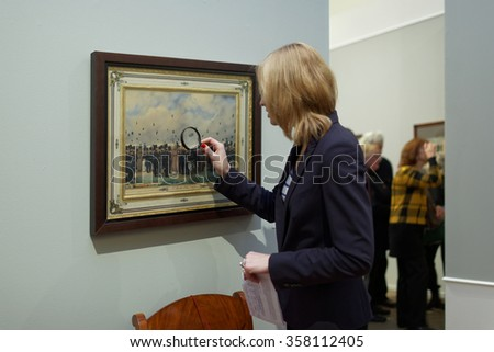 ST. PETERSBURG, RUSSIA - OCTOBER 22, 2015: Woman with magnifier in the exhibition of Pavel Fedotov, 1815-1852, in the Russian Museum. The exhibition is dedicated to 200th anniversary of the painter