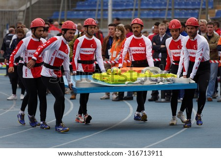 ST. PETERSBURG, RUSSIA - SEPTEMBER 9, 2015: Team Turkey bring fire hoses before competitions in combat deployment during XI World Championship in Fire and Rescue Sport - stock photo