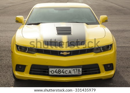 St. Petersburg, Russia - September 27, 2015: Yellow Chevrolet Camaro car stands parked on the roadside. Front view - stock photo
