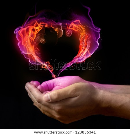 St. Valentin's burning heart on the hands against dark background - stock photo