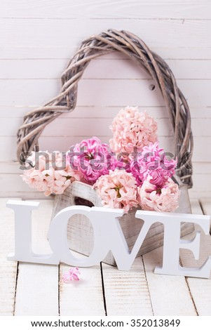 St. Valentine Day or  love concept. Fresh spring hyacinths flowers in box and word love on white wooden background. Selective focus.