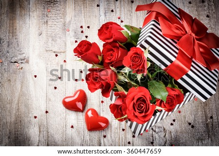 St Valentine's setting with bouquet of red roses in retro gift box. Copy space - stock photo
