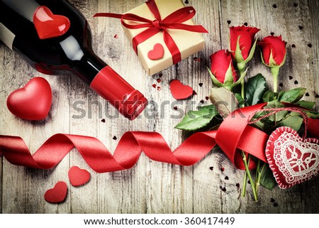 St Valentine's setting with red roses bouquet, present and red wine bottle. Copy space - stock photo