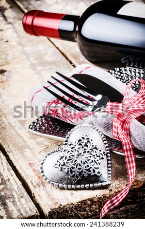 St Valentine's table setting with red wine and festive decoration - stock photo